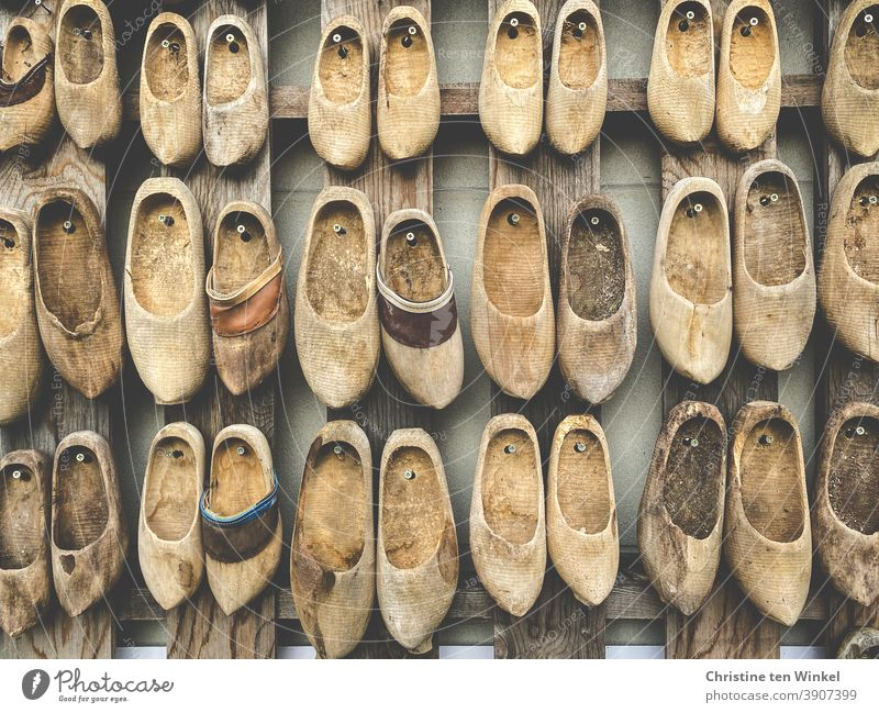 A lot of old wooden shoes, clogs, Münsterländer wooden lumps are decoratively attached to a wall. Wooden shoes Clogs Munsterlander lump of wood Old Second-hand
