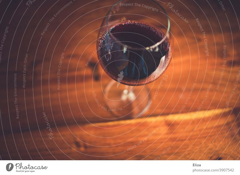 A glass of red wine on a wooden table Red wine Vine Wine glass Wood Redwine glass Alcoholic drinks Wooden table Table plan Bird's-eye view