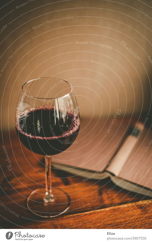 A glass of red wine and an open book. Time for yourself. Book Vine Glass Reading Wine glass Red wine relaxation Alcoholic drinks Time to yourself To enjoy