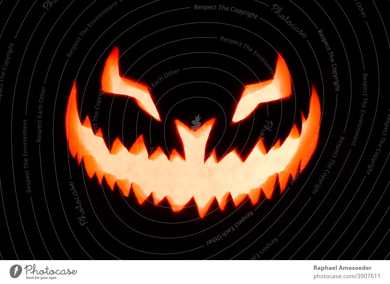 Carved pumpkin glowing in the dark autumn burning candle carved celebration creepy decor decoration evil face fall fear fire flame fruit funny grinning