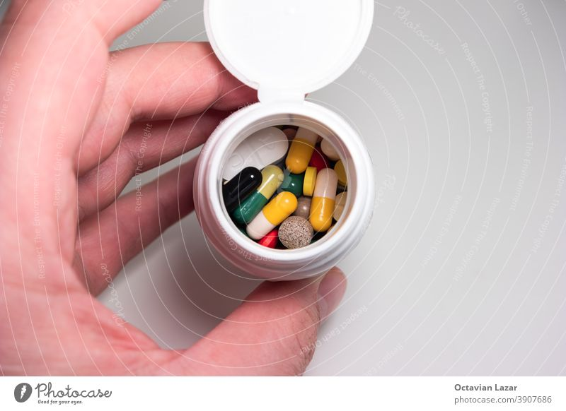 Caucasian male hand holding a white plastic medicine bottle with a colorful variety of medical capsules and pills top view supplement epidemic drugs pile