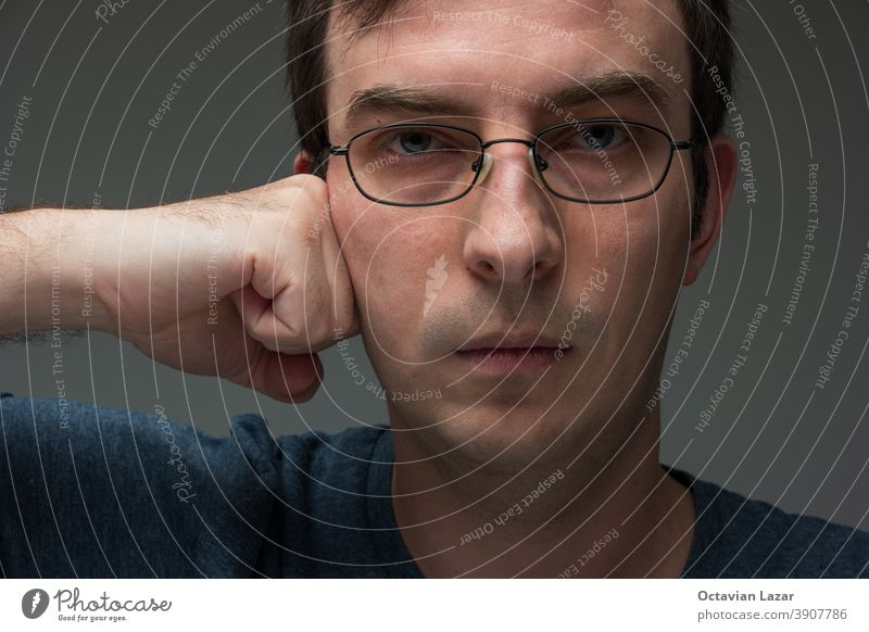 Caucasian male with glasses with clinched fist pressed against cheek looking at camera 30 to 40 years old awareness pain emotion alone stressed caucasian