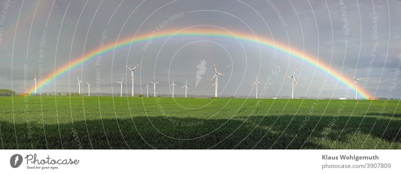Beautiful rainbow over a wind farm near Friedland Rainbow Pinwheel windmills Field Sky Grain field Renewable energy wind power Energy industry Electricity