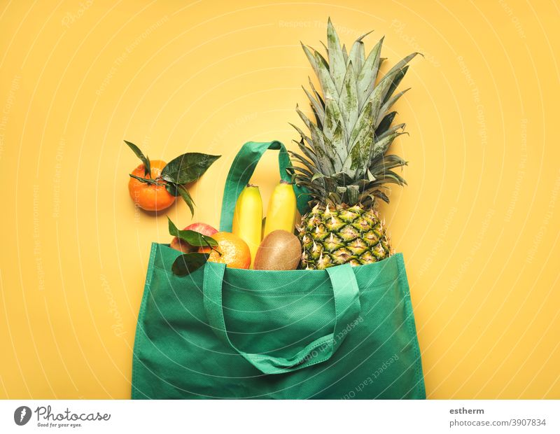 green shopping bag with different fruits,pineapple, bananas, oranges, kiwis and apples fruit store juice ingredients vegan products diet eco natural ecologic