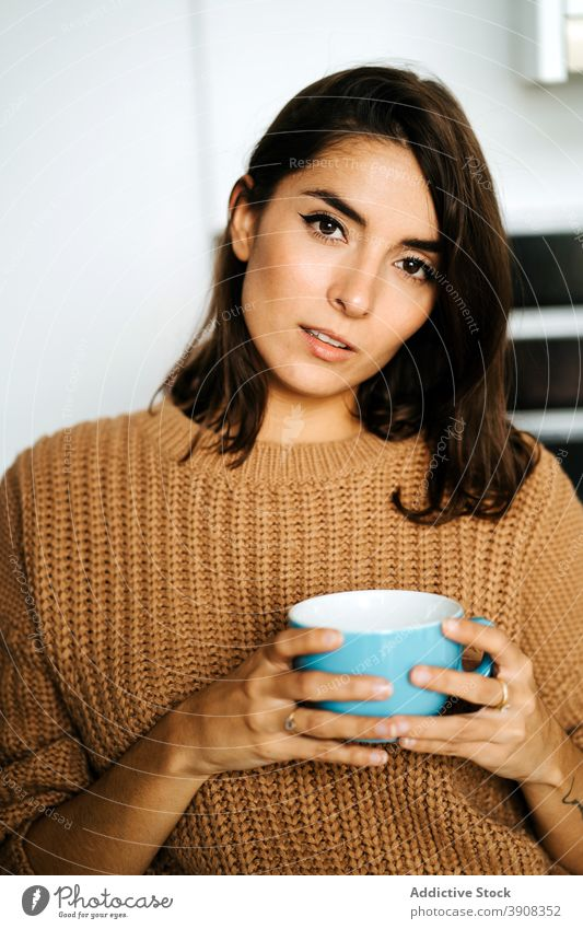 Woman with cup of beverage relaxing in kitchen woman coffee home tranquil drink enjoy domestic weekend female mug chill calm apartment cozy peaceful hot drink