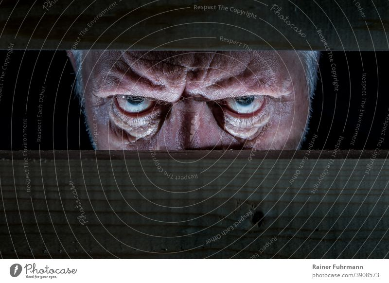 A man looks evil through a wooden barricade Man Evil portrait Eyes Human being Looking Face Fear Freak Force Aggression Aggravation Anger Dark Heartless