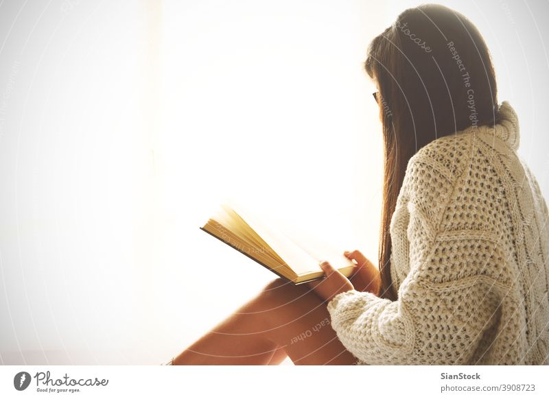 Young woman sitting in bed while reading a book window view lazy sunday winter coffee cup tea glasses morning girl home relax socks beautiful young bedroom