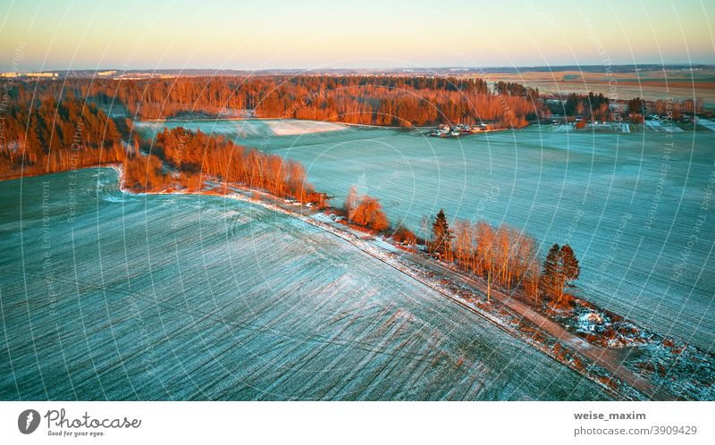 Colorful trees December sunset Aerial scene. Rural dirt road. Countryside top view. field snow winter crop aerial agriculture evening nature landscape covered