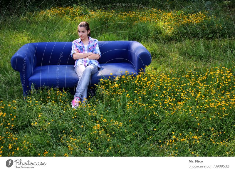 Young girl sits on a blue sofa which stands on a meadow Sit tranquillity relaxing relaxed portrait Happy Wait Grass Nature Environment Sofa Meadow naturally