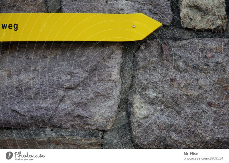 the right direction Signage Wall (barrier) Signs and labeling Characters Facade Yellow Gray Seam Stone wall Natural stone Trend-setting Direction writing Arrow