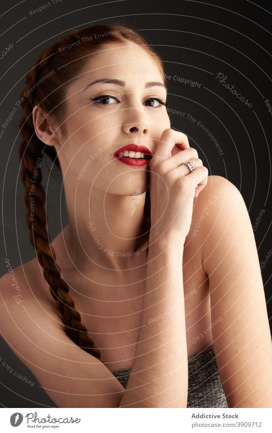 Woman with braids in studio looking at camera redhead hairstyle woman appearance charming trendy red hair female red lips model personality individuality