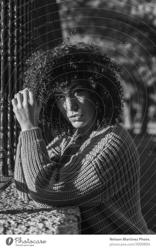 Grayscale shot of a beautiful female with curly hair standing near a metallic fence. portrait Black & white photo woman afro hairstyle black young casual
