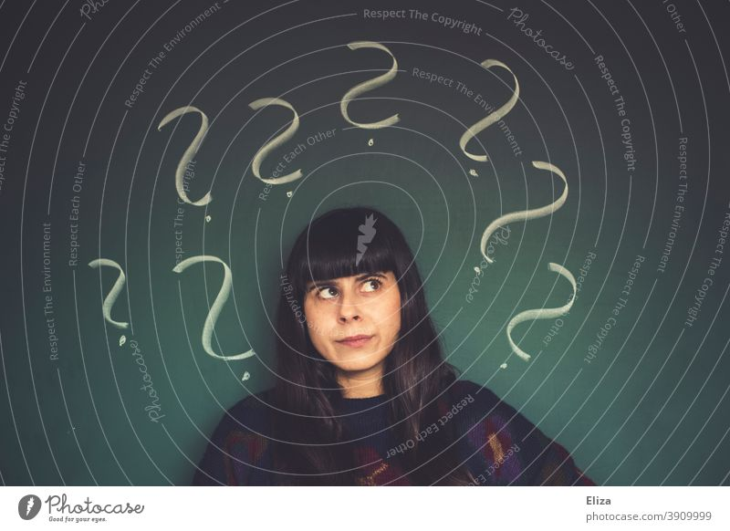 Young woman with many question marks seems perplexed and confused Question mark Perplexed dishevelled disorientation Ask Disorientated Irritation Insecure