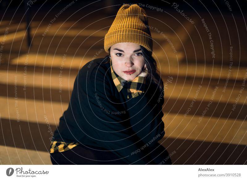 Junge Frau mit Mütze hockt nachts angeleuchtet in orangem Laternenlicht auf einem Zebrastreifen in der Stadt jung Jugendliche Straße draussen bunt