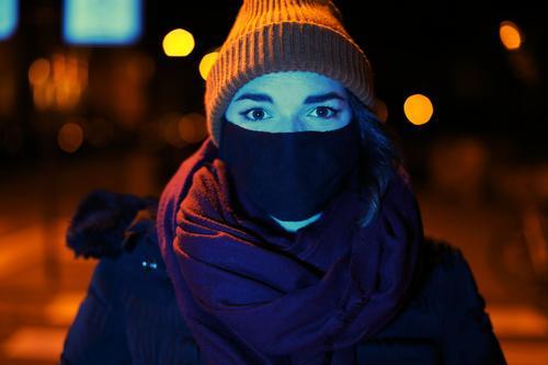 Junge Frau mit Maske und Mütze steht nachts mit blauem Licht angeleuchtet in orangem Laternenlicht in der Stadt jung Jugendliche blaues Licht Straße kariert