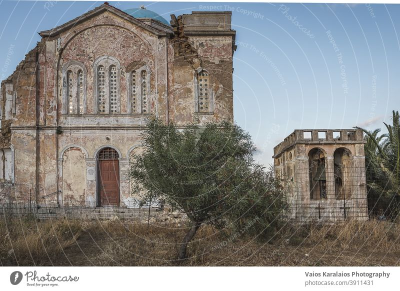 An orthodox church devasteted by an earthquake, in the village Mitata of island Cythera, in Greece. The bell on the right and in the foreground an olive tree.