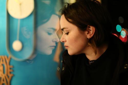 Junge Frau schaut nachts in ein Schaufenster und ihr Gesicht spiegelt sich darin jung Jugendliche Straße draussen bunt Stadt Stadtlandschaft dunkel Lichter