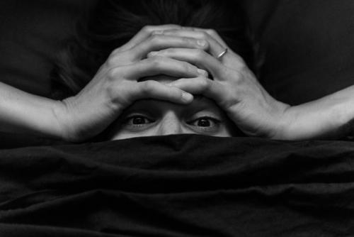 A young woman covers her head with her hands, her nose and mouth are covered by dark sheet. She has intense eyes. portrait hidden Covered Experimental Feminine