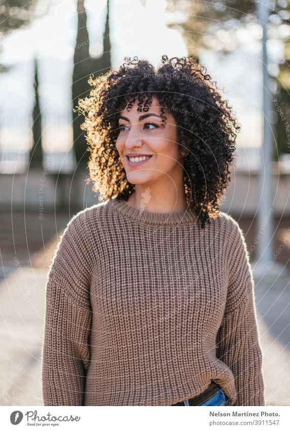 Beautiful female with curly hair in a park wearing a beige sweater and smiling. sunlight fashion portrait afro woman real woman human being ethnicity hairstyle