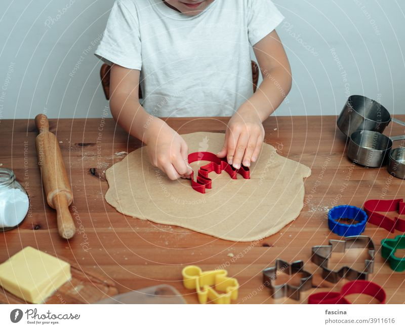 Son in kitchen making cookies christmas cooking preparation deer child kid family baking boy gingerbread caucasian son bake pastry flour fun sweet homemade