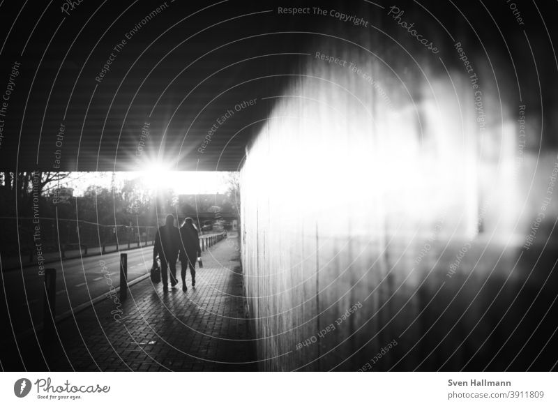 Silhouettes pair walking through tunnel towards the sun Couple people Man Woman Romance Love Connectedness Safety (feeling of) Sunlight solar star Tunnel