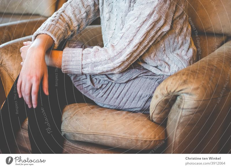 A young woman sits slouched in a faded brown leather chair with her legs crossed. She wears a grey cable-knit sweater, a grey pleated skirt and black stockings. Portrait without head