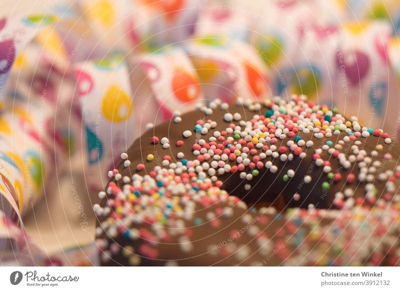 Donut / Doughnut with chocolate and sugar pearls. Behind them streamers with balloon motive in close-up. Weak depth of field with focus on the sugar beads
