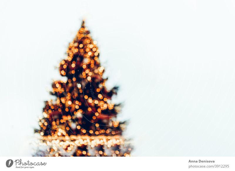Defocused christmas tree with bokeh background xmas new year holiday celebration invitation white seasonal festive decoration card snow eve winter