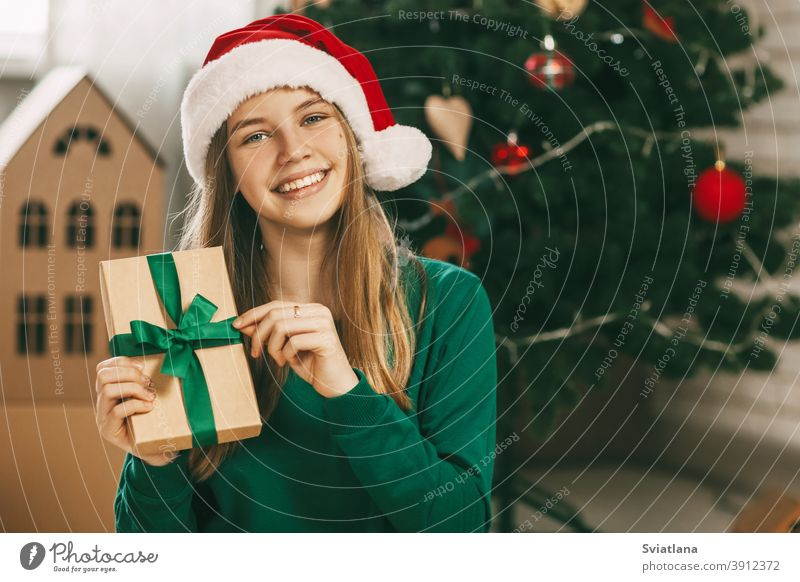 A beautiful little girl looks at the camera and smiles, holding a kraft paper gift tied with a green ribbon in her hands. Christmas mood. Concept for New Years holiday at home.