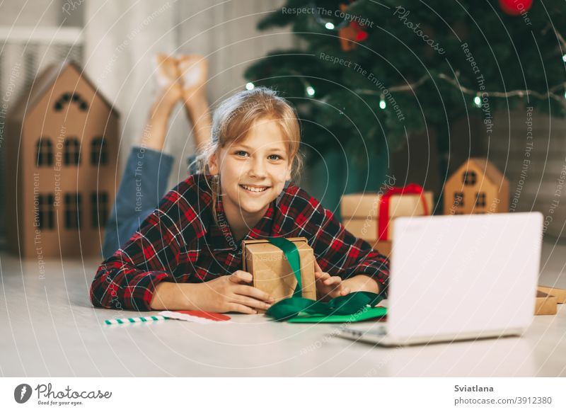 A happy little girl opens a gift under the Christmas tree at home and communicates with her grandparents via a laptop via video link. Holiday concept for Christmas and New Year at home.
