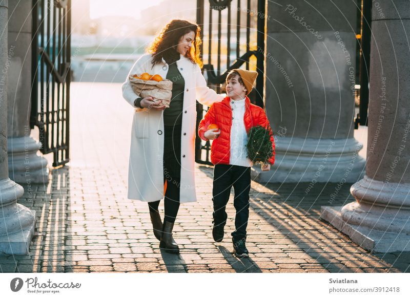 A beautiful mother with her son in a bright orange jacket and a fashionable yellow hat are walking from the store holding a package of oranges and a small Christmas tree. Shopping for the holiday. Preparing for Christmas and New Year