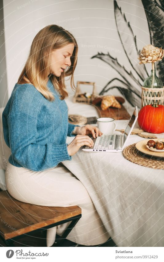 Cute blonde girl working in the morning on a laptop and drinking coffee. Work online, freelance, social distance using beautiful kitchen woman lifestyle