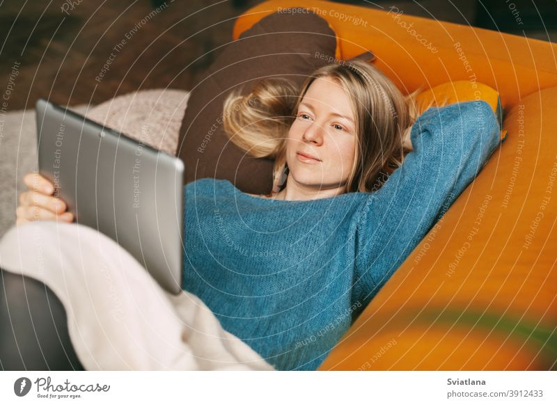 Happy girl lying on a comfortable sofa in the living room, watching a movie on a tablet. A young woman has a rest and communicates with friends using a tablet. Work online, freelance, social distance