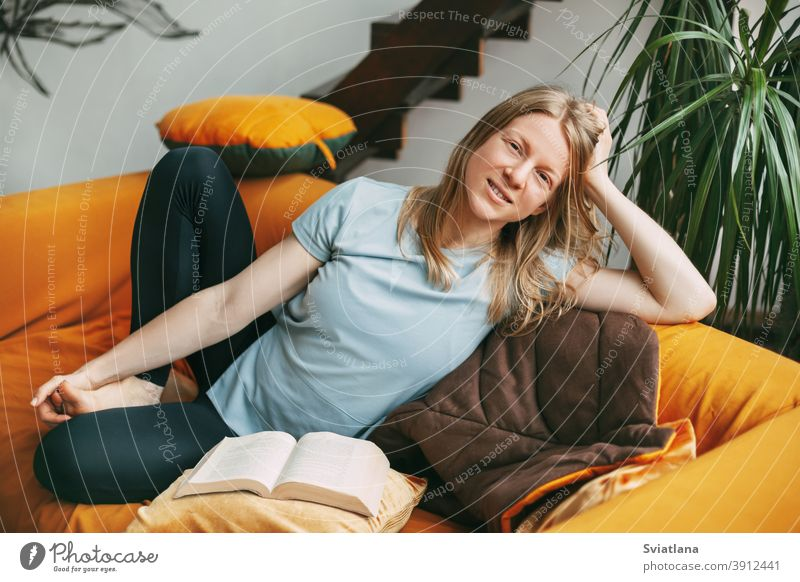 A young woman is sitting on a comfortable sofa in the room and smiling, with an open book next to her. The girl ponders what she has read in the book. home