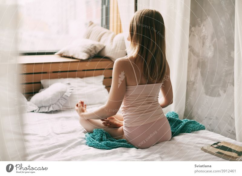 A young woman in pyjamas is sitting on a bed in a Lotus position with her fingers folded in a mudra gesture, enjoying a morning of deep mindfulness meditation. Rear view