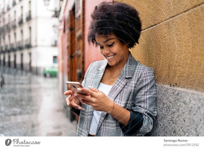 Pretty Afro Woman Using Phone woman afro portrait black woman using phone street city life cellphone smartphone communication technology type typing texting