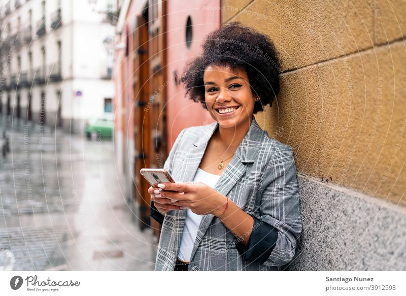 Pretty Afro Woman Using Phone looking at camera woman afro portrait black woman using phone street city life smiling cellphone smartphone communication