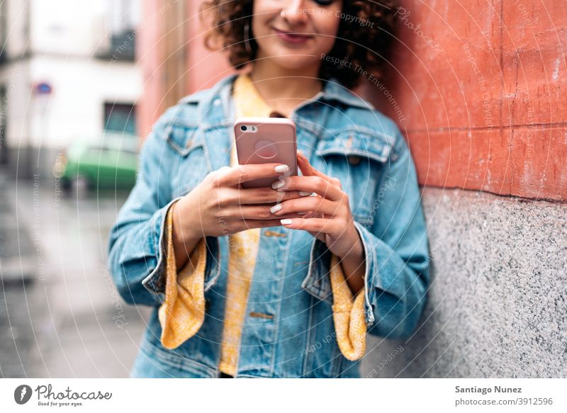 Young Woman Using Phone caucasian curly hair unrecognized faceless young woman using phone street city life smiling happy cellphone smartphone communication