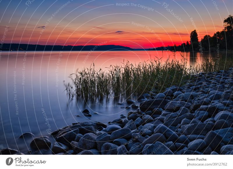 The sun bathes Lake Constance in a brilliant red Sunset reflection idyllically Deserted Red Mystic romantic sunset Water Sky Landscape Nature Sunrise Ocean Dusk