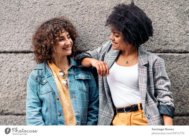 Cool Afro Girl and Friend Smiling women looking at each other street multi-ethnic afro girl caucasian portrait having fun front view friends friendship