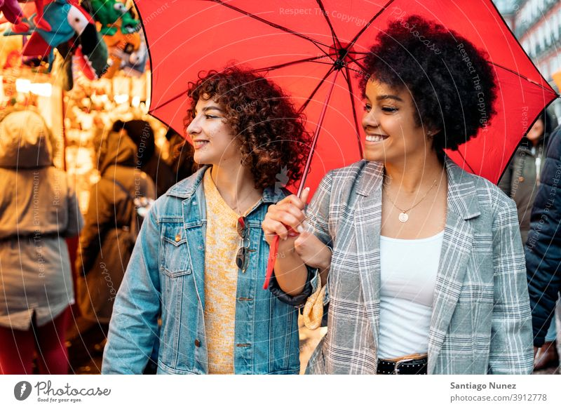Happy Friends in Rainy Day umbrella rainy day friends afro girl black woman caucasian city life smiling front view portrait women looking street multi-ethnic