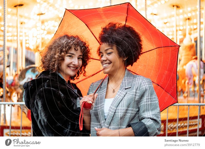 Happy Friends in Rainy Day umbrella rainy day friends afro girl black woman caucasian city life smiling front view portrait women looking at camera carousel