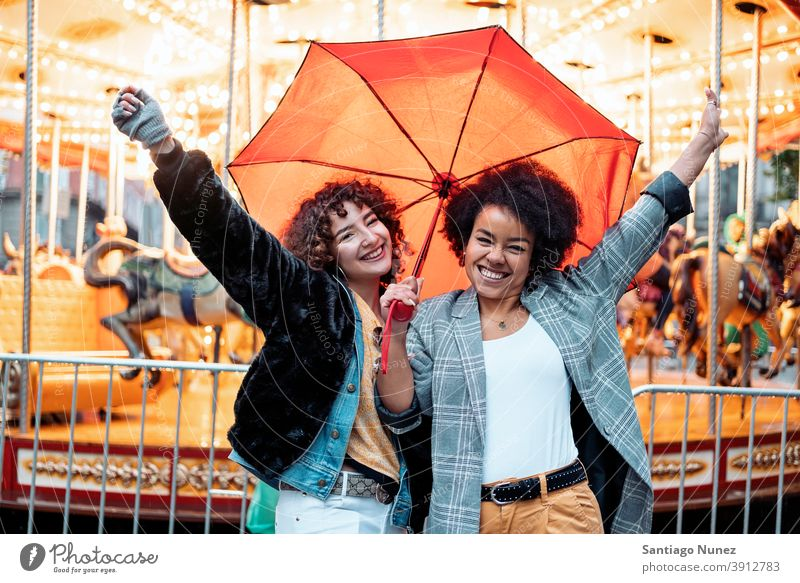 Cheerful Friends in Rainy Day umbrella rainy day friends afro girl black woman caucasian city life smiling front view portrait women looking at camera carousel