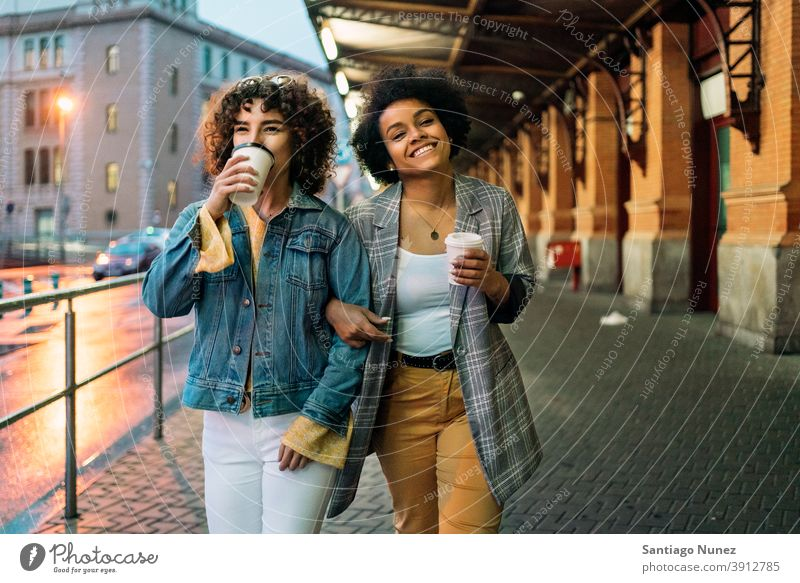 Afro Girl and Friend in Street cup of coffee walking street friends drinking looking at camera women multi-ethnic afro girl caucasian portrait having fun