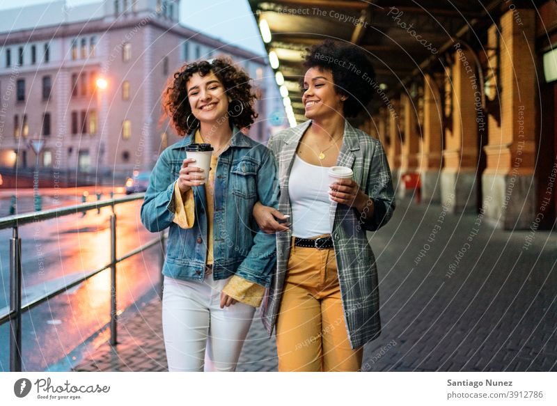 Afro Girl and Friend in Street cup of coffee walking street friends drinking women multi-ethnic afro girl caucasian portrait having fun front view friendship