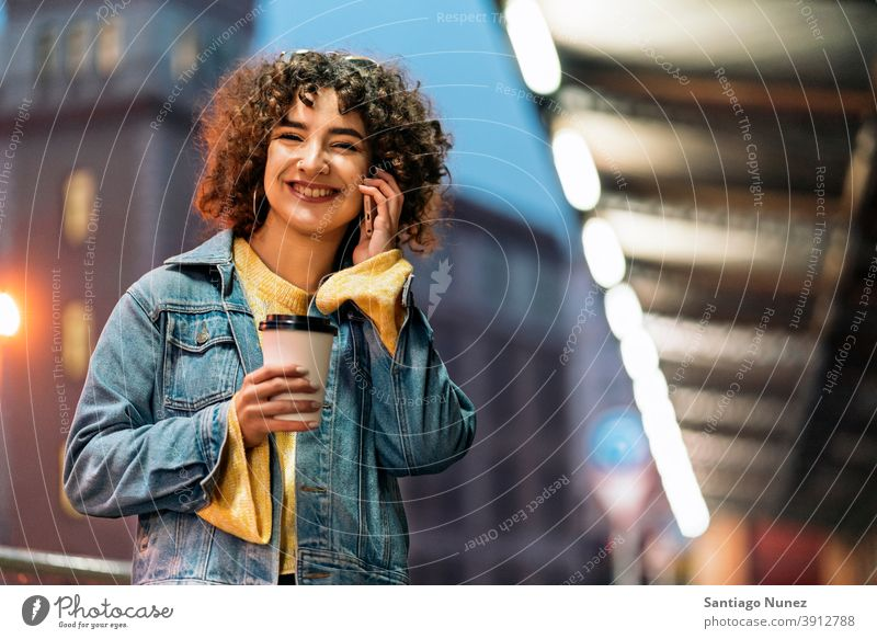 Happy Young Woman Using Phone copyspace standing using phone phone call calling cup of coffee front view portrait girl woman young 20s curly hair female street