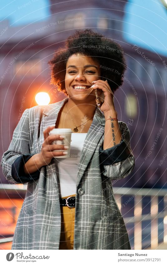 Happy Afro Woman Using Phone standing using phone phone call calling cup of coffee front view afro portrait black woman street city life cellphone smartphone