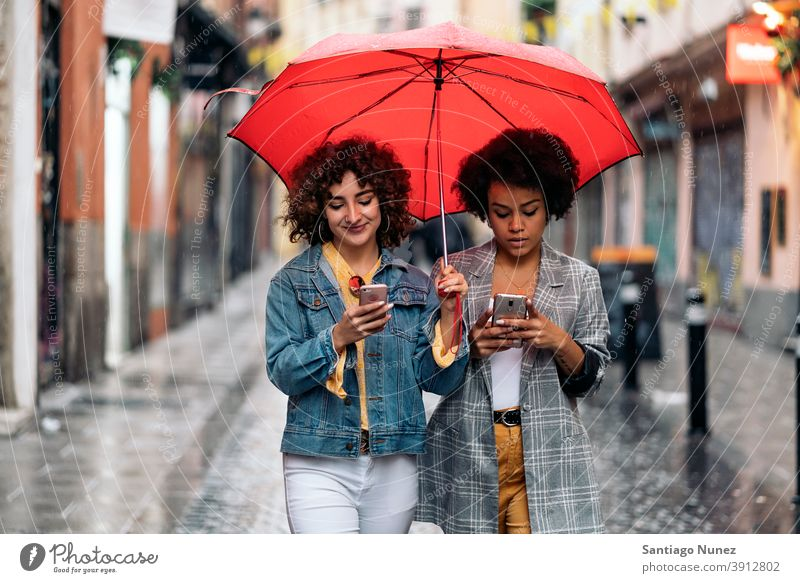 Happy Friends Using Phone umbrella rainy day friends afro girl black woman caucasian using phone city life smiling front view portrait women looking