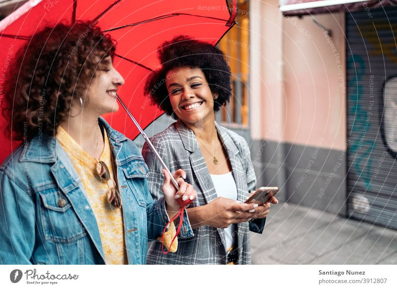 Happy Friends in Rainy Day umbrella rainy day friends afro girl black woman caucasian using phone city life smiling side view portrait women