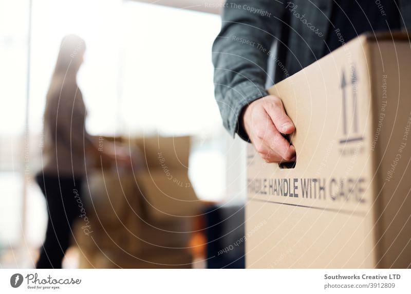 Close Up Of Man Carrying Removal Box As Couple Move In Or Out Of New Home couple young couple house buying packing moving out moving house upgrading carrying